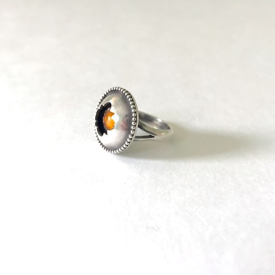 The Amber ShadowBox ring is made from a amber stone set in sterling silver.  The shadow box has a hand cut design and a row of silver pebbles  boarding.The face measures 17mm in diameter.The ring base is made from  sterling silver and is a size 6 (measurements are approximate, this is a  one of a kind handmade item)  >>>Silver is a metal known to conduct lunar energy, mystery, and the  unconscious. It's associated with the element of earth and activates all  seven main chakras in the…