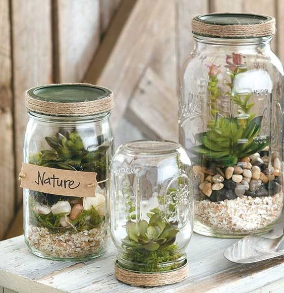 DIY Mason Jar Crafts - With a few crafty touches, you can turn ordinary jars and bottles into charming home accessories, cute gift containers, clever keepsakes, and helpful organizers. All you need is a little paint, some jute or burlap, labels or tags, or other trims.   Easy projects in DIY Mason Jar Crafts include Terrariums, a Storage Shelf with hanging jars, a monogrammed Kitchen Storage jar, glittery Tablescape Jars, a Travel Savings Jar, Beach Memory Jar, Sand Collection Bottle, Ship...