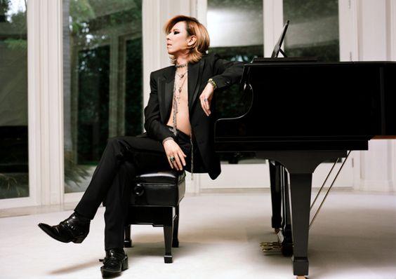 黒いジャケットを着てピアノに肘をついているXJAPAN・YOSHIKIの画像