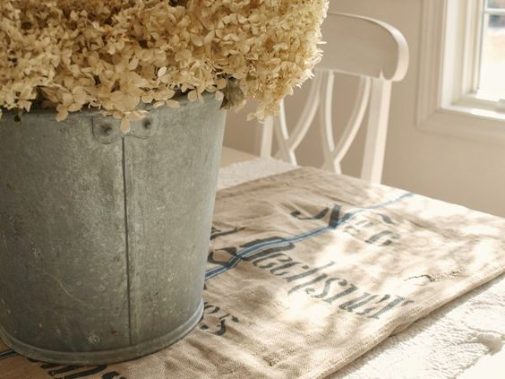 Vintage German grainsack used as table runner (A Beautiful Mess)/white romantic shabby chic dining room/galvanized bucket with hydrangea/white Swedish chair/Hello Lovely Studio