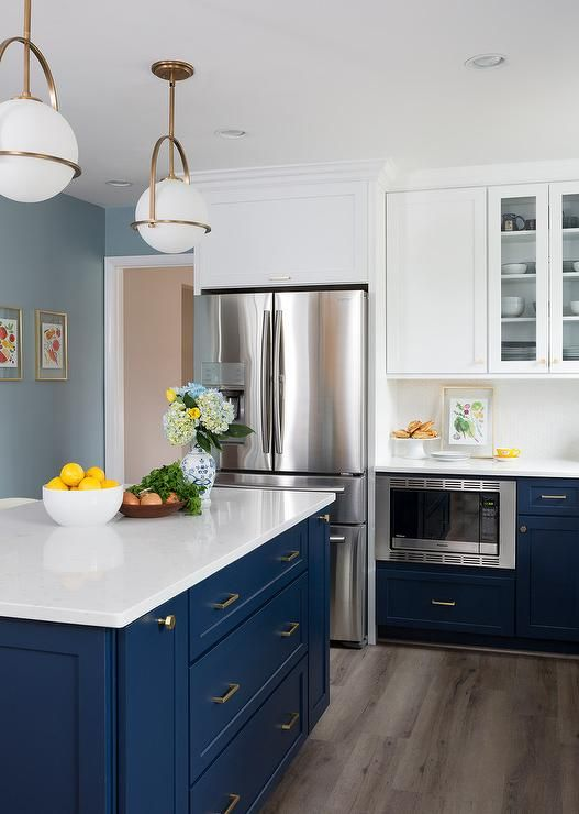 A Navy Blue Center Kitchen Island Is Lit By Gold And White Pendant