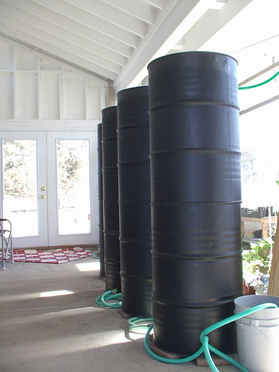 These barrels collect water off the roof where it heats up warming the greenhouse in the winter.: