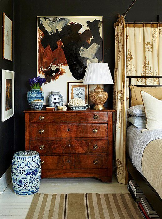 Want to give your bedroom an instant update? Try painting your walls a matte black.