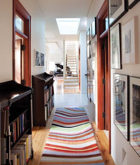 Colorful rugs, slim bookshelves and a gallery of artwork make an interesting entry out of what could otherwise be a cold corridor.