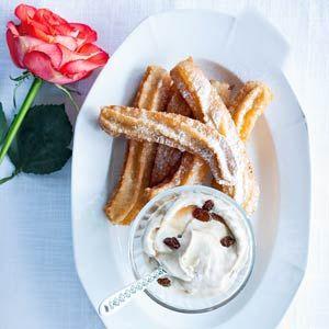 Spaanse churros met kaneel / - 25 g suiker   - 50 g boter    - 125 g bloem    - 2 eieren    - 1 tl kaneel    - 175 ml zonnebloemolie    - poedersuiker, om te bestrooien