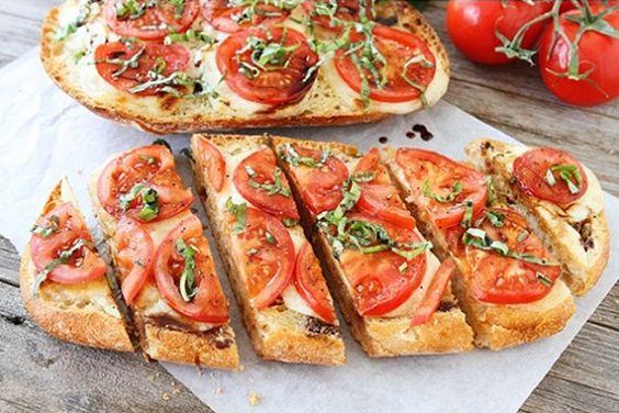 Bruschetta Caprese 1 pão italiano, cortado horizontalmente pela metade; 4 colheres de sopa de manteiga com sal ; 3 dentes de alho picados; 150g de mussarela de búfala fatiada; 1/2 xícara de vinagre balsâmico; 2 tomates médios, cortados em rodelas; Sal e pimenta do reino à gosto; 1/3 xícara de manjericão fresco picado;: