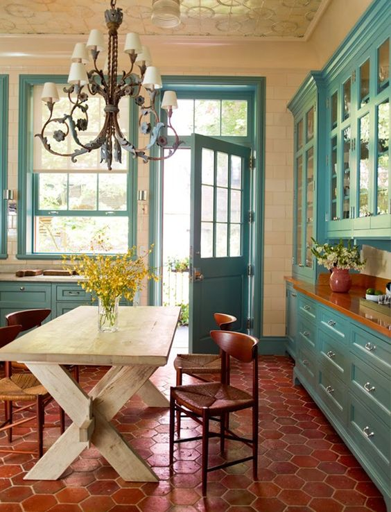 Turquoise kitchen cabinets and trim. The colorful kitchen resides in a Greenwich Village townhouse designed by Brian Sawyer and John Berson of Sawyer | Berson–the architecture, landscape architecture and interior design firm based in New York City.
