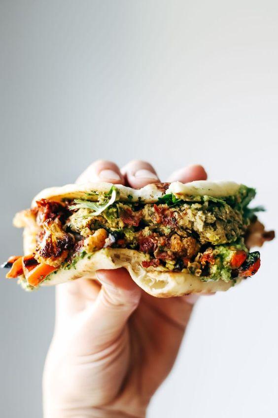 Naan-wich: 5 ingredient falafel, roasted veggies, and avocado sauce stuffed between pillowy garlic naan. Best sandwich recipe I've ever made. Vegetarian / Vegan. | pinchofyum.com