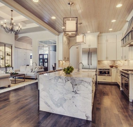 The waterfall style of this kitchen island brings even more of that white marble to the forefront. You can see it and really experience the luxury alongside the pendant lights and hardwood floors.
