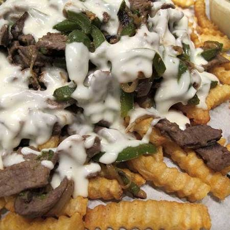 A savory steak, pepper, & onion mixture coated in a creamy, cheesy sauce all resting on a mound of crispy crinkle-cut fries. Philly Cheesesteak Fries can shared with friends at your Super Bowl gathering or, if you're like me, just make them for dinner. | eatatkates.com:
