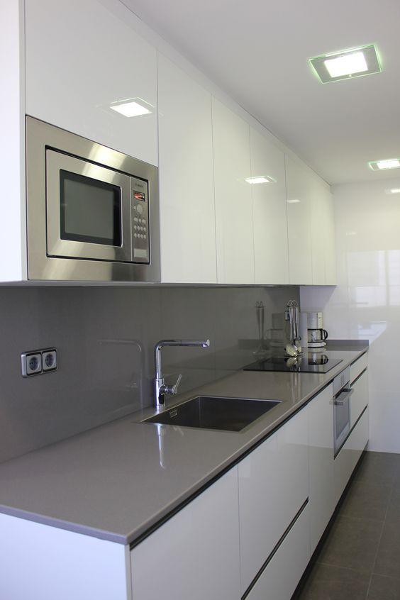 Cocina con mobiliario en T2 blanco cristal combinado con mármol Silestone gris expo pulido. Acabados de gres porcelánico para los paramentos verticales y horizontales.