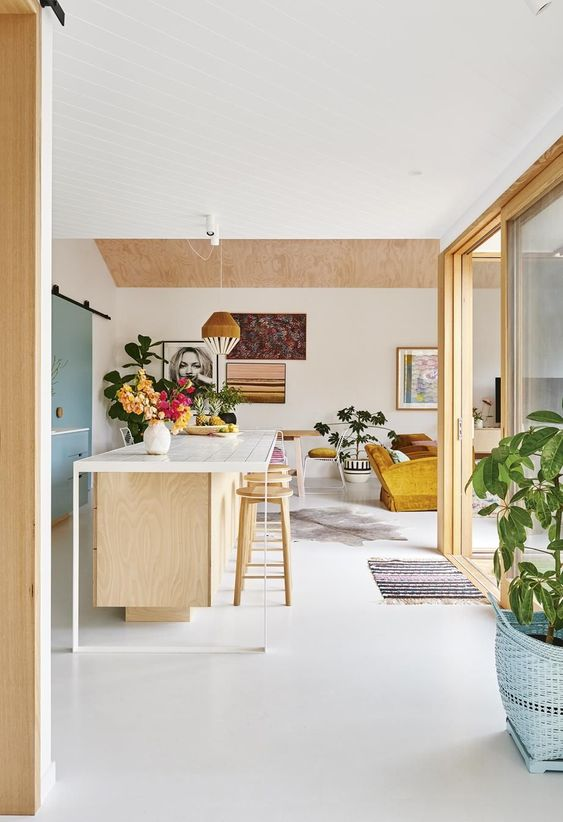 Plywood kitchen with white kitchen island and pops of pastel colour.