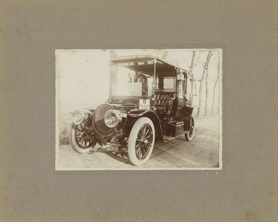 Anonymous | Man in automobiel, nummer 118, voor huis, Anonymous, 1900 - 1920 |