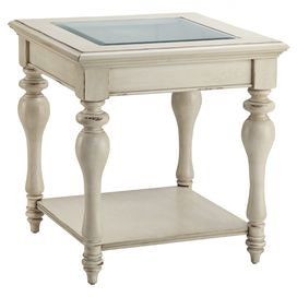 """Glass-topped end table in cottage white with turned legs and a bottom display shelf.     Product: End tableConstruction Material: Poplar solids, birch veneer and glassColor: Cottage whiteFeatures: Bottom display shelf    Dimensions: 25"""" H x 23.75"""" W x 23.75"""" D"""