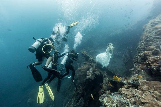buzos ayudando a chica posando en el mar