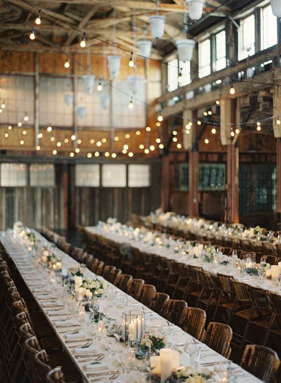 wedding receptions in a barn with hanging lights and candles for rustic themed wedding ideas