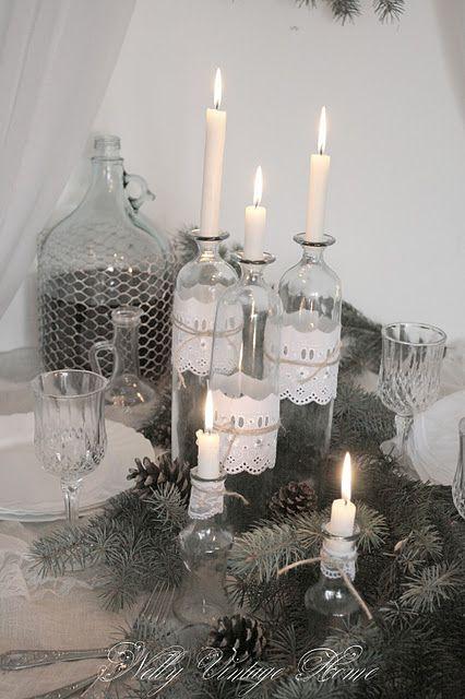 Des bougies dans des bouteilles de verre entourées de broderie anglaise, trop chou avec le petit noeud en ficelle.: