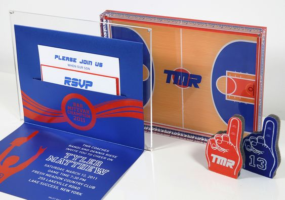 A basketball themed Bar Mitzvah invitation. The custom acrylic box was designed to replicate a basketball court with cheering fans. A foil stamped invitation and mini foam fingers completed the look.
