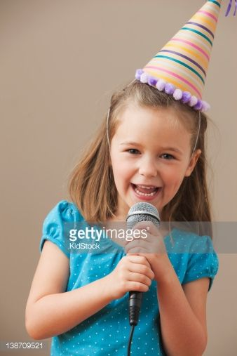 Stock Photo : Caucasian girl in party hat singing into microphone