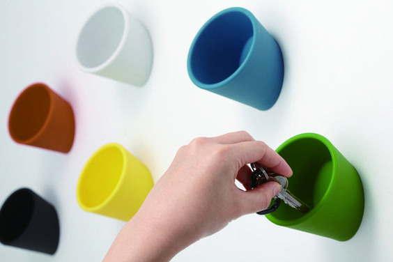 Here's a neat little solution for storing all those miscellanous things you keep in your pockets or that tend to lie around. Ideaco's Cuppo is a cup designed to be attached to a wall or other vertical surfaces.