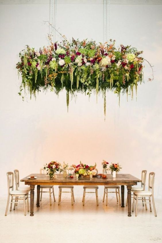 Decorate your wedding with suspended flower garlands ad keep your table setting simpel to create maximum effect.: