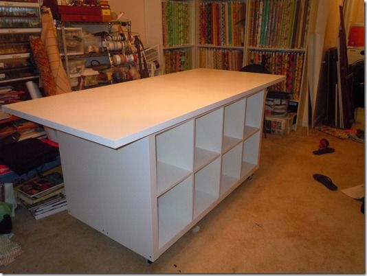 Wicked sewing table made of Ikea pieces. Two Kallax shelving units, back-to-back, with a table top (you can order table tops separate from legs or choose legs to go with any table top).
