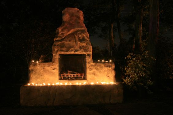 Simple votive uplighting on our outdoor fireplace at Goldner Walsh Garden & Home