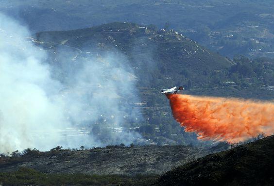 Sebuah pesawat menjatuhkan air di lokasi kebakaran hutan di kawasan perbukitan dekat San Marcos, California.