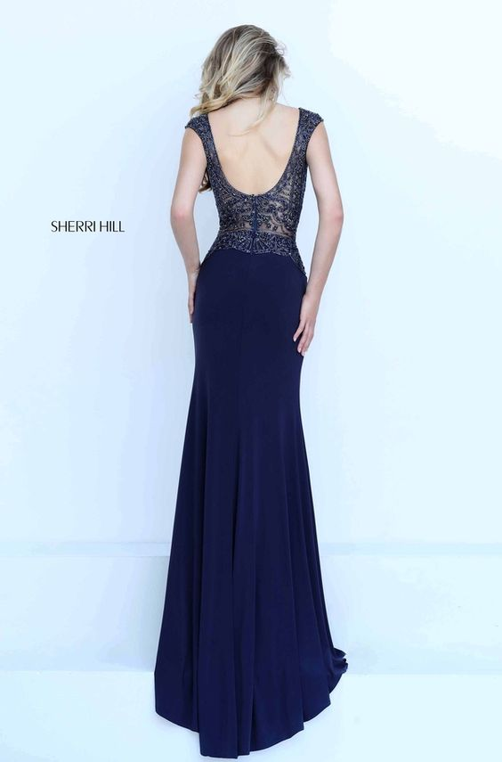 Glamorous yet risque, the Sherri Hill full-length 50159 prom dress adds a touch of dare to the evening. Exquisitely beaded lace creates an illusion bodice with integrated bra cups. It showcases a curved V-neckline framed with cap sleeves and a scoop back. The beaded lace accents the top of the skirt, creating a scalloped edged dropped waistline. The long skirt features a provocative high-thigh side slit and flows into a soft sweep train, completing the jersey silhouette.