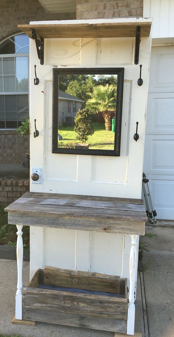 Hall tree made from an old door with table and storage underneath. It has a shelf and hooks too. The doorknob is antique metal