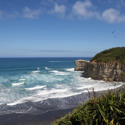 The World's Most Colorful Beaches: Muriwai Beach, Aukland, New Zealand. While there are a number of spectacular black beaches in the world, how many also sparkle? Muriwai's stunning black sand comes from a mix of materials (including iron and titanium) from the area's ancient volcanoes.