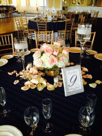 Clear cylinder arranged white hydrangea and peach roses surrounded by rose petals. doristhefloristt.com