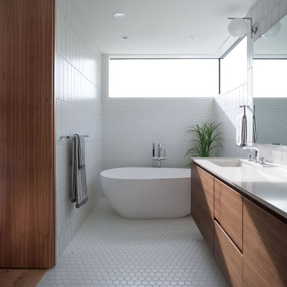 This bathroom features a walnut vanity with a white countertop. Two different styles of white tiles have been included in the design.