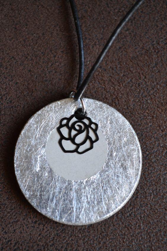 """Collier en béton rond """"Black rose"""" - Collection """"Black & White"""" de Sésé'Dille.  Ce collier est composé d'un pendentif rond en béton recouvert d'une feuille de métal argenté, d'une breloque en métal rose noire et d'un cordon en cuir de 3 mm."""