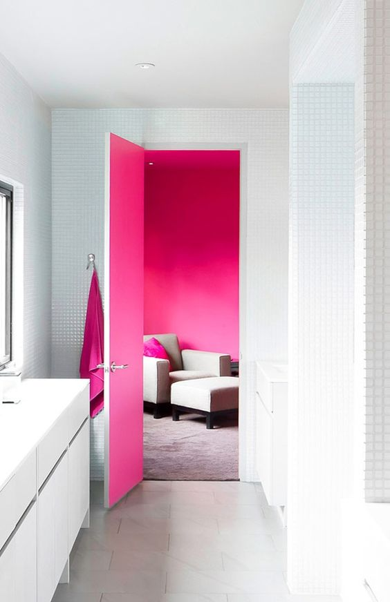 A pristinely white bathroom that gets a splash of magenta only when the door is open