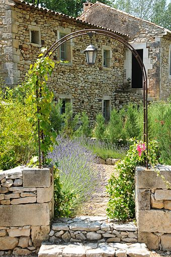 Charming stone  #TuscanHome garden gate and pebble path.  Romantic living.  I love the wrought iron arch with hanging lantern.:
