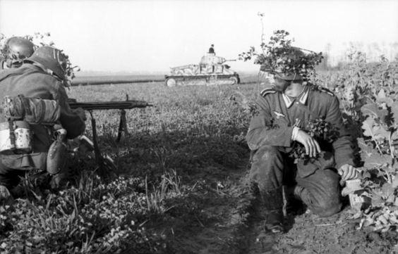 Juni 1944 - Frankreich/Belgien (Flandern).- deutsche Infanteristen mit getarnten Stahlhelmen und Maschinengewehr 42, im Hintergrund erbeuteter französischer Panzer Somua S-35 der deutschen Wehrmacht im Gelände
