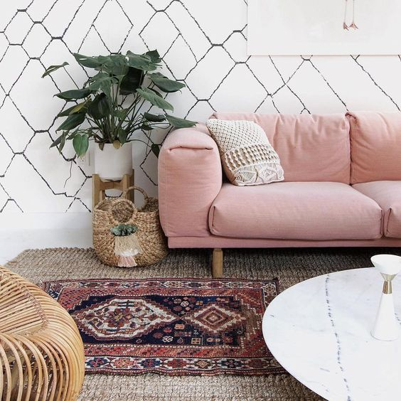 Boho living room with plant on raised stand by Beachy Boheme