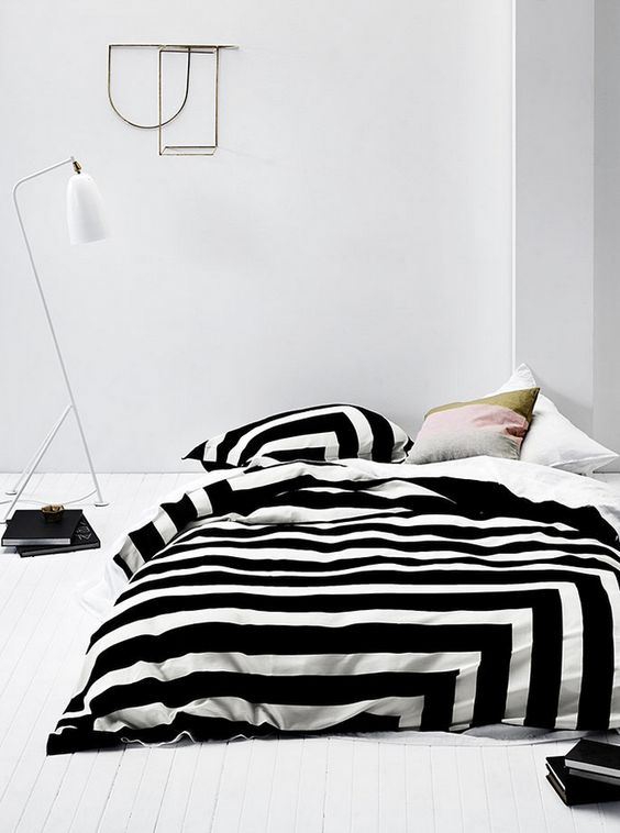 Lacquered white floor, Gubi Grasshopper Lamp paired with some seriously striped linens. Subtly feminine without exaggerated overtones. I like this: