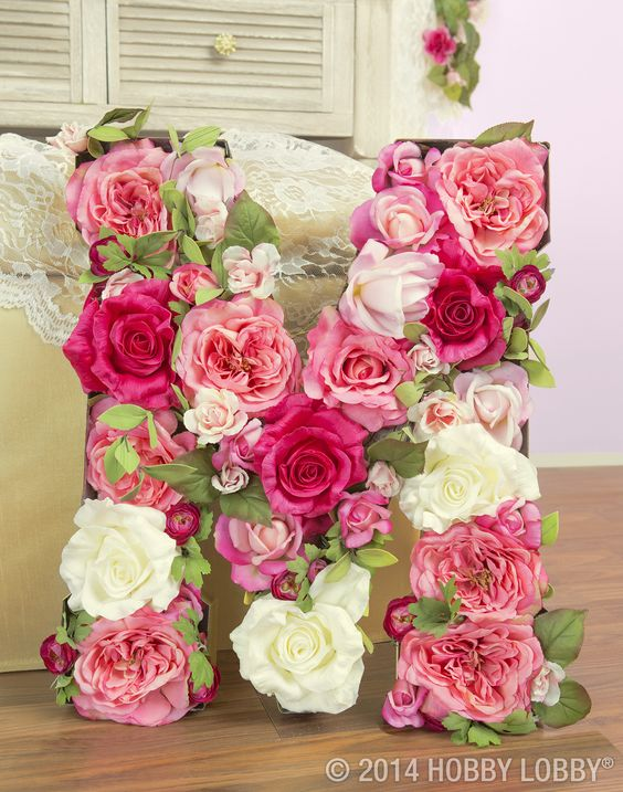 M is for monograms! Make your own floral letter with these easy steps. 1) Lay paper-maché letter flat on work surface. 2) Cut along edges to remove front of letter. 3) Paint desired color. 4) Fill hollowed-out letter with roses and greenery.