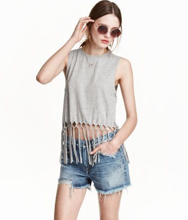 Short tank top in jersey with a printed motif at front. Long fringe at hem and raw edges at armholes.
