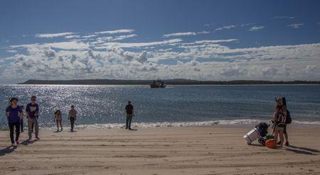 Bereits der Fähranleger in Rainbow Beach am Inskip Point besteht nur aus Sand. Die Autofähre nähert sich gerade von Fraser Island her. Rechts im Bild warten zwei Wanderer mit großem Gepäck, die anderen Fußgänger gehen gerade zurück zu ihrem Geländewagen