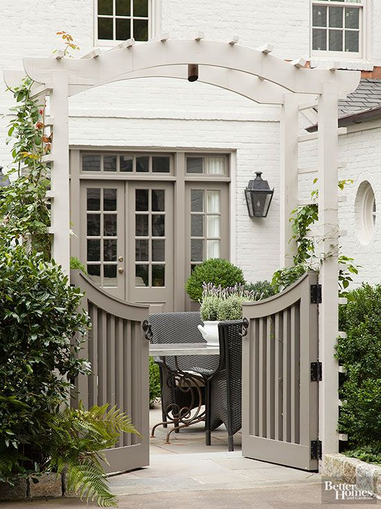 If you want to separate your outdoor space from your driveway or a street but you want to maintain accessibility, consider a gated arbor. These homeowners opted for a shorter, curved-top gate to create separation without blocking views. A mix of bright whites and cool grays give the space an elegant and sophisticated look.
