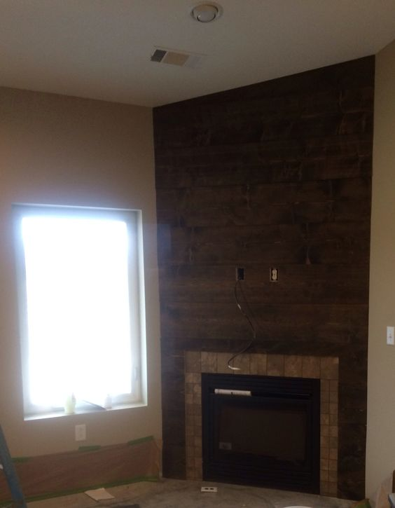 Shiplap corner fireplace with a stone border around the ...