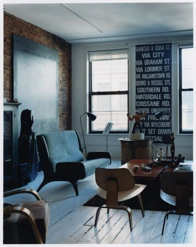 Black and brown living room, Eames Plywood chair, Bus sign artwork (I love this but...I would throw in at least one large pop of color, with one small matching accent. Like a huge red clock and a little red vase?)