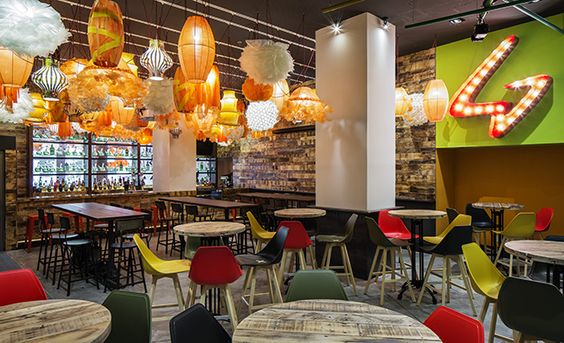 Generator Hostels Barcelona, Spain In the bar, Generator's signature 'G' is interpreted through light. Tables and walls made of reclaimed wood shipping pallets encourage a casual feeling.