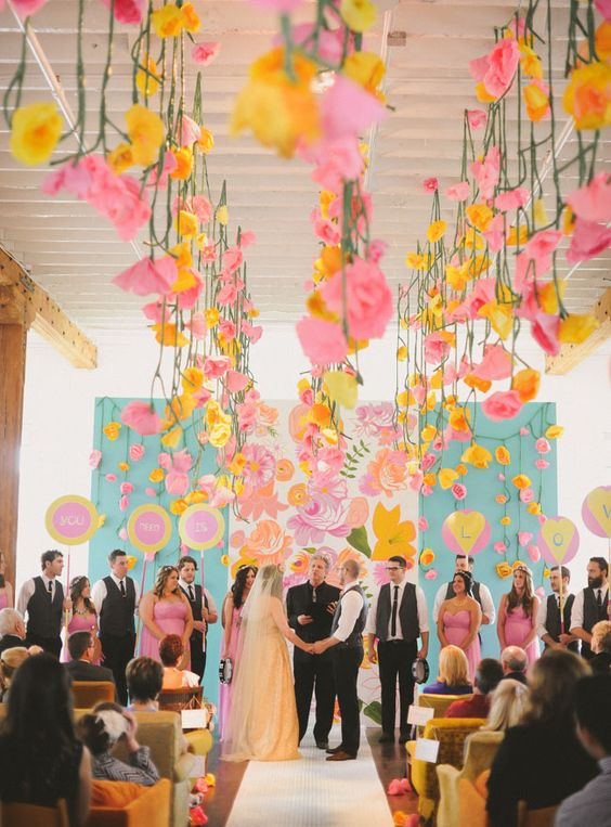 colorful ceremony with paper flowers strung from the ceiling and a hand painted backdrop