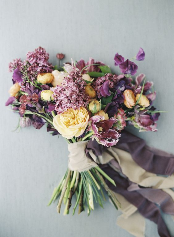 Could this Kelly Oshiro bouquet be any prettier? She arranged garden roses, ranunculus, lilacs, tulips and sweet peas for what just might be the loveliest orange and purple display ever.