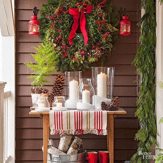 Make the most of sheltered porch corners with an impressive (and easy!) display of candles and greenery. To get the look, top a small table with a patterned holiday towel, assorted candles, and pinecones. A festive holiday wreath and bucket of birch branches completes the look./