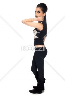 side view of a young indian woman looking at camera. - Side view portrait of a young indian woman looking at camera while standing over white background, , Model: Kiran Bahugun